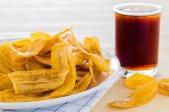 Sobremesa, microplaquetas da banana e bebidas Foto de Stock Royalty Free