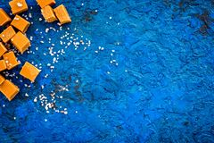 Sobremesa na moda Caramelo salgado Cubos do caramelo polvilhados por cristais de sal no espaço azul da cópia da opinião superior  imagem de stock