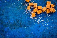 Sobremesa na moda Caramelo salgado Cubos do caramelo polvilhados por cristais de sal no espaço azul da cópia da opinião superior  imagens de stock