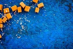 Sobremesa na moda Caramelo salgado Cubos do caramelo polvilhados por cristais de sal no espaço azul da cópia da opinião superior  imagem de stock royalty free