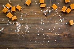Sobremesa na moda Caramelo salgado Cubos do caramelo polvilhados por cristais de sal no espaço de madeira escuro da opinião super imagem de stock royalty free