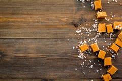 Sobremesa na moda Caramelo salgado Cubos do caramelo polvilhados por cristais de sal no espaço de madeira escuro da opinião super imagens de stock