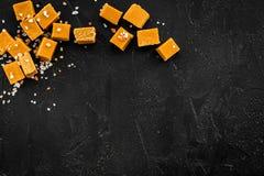 Sobremesa na moda Caramelo salgado Cubos do caramelo polvilhados por cristais de sal no espaço preto da cópia da opinião superior fotografia de stock royalty free