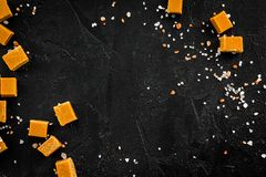 Sobremesa na moda Caramelo salgado Cubos do caramelo polvilhados por cristais de sal no espaço preto da cópia da opinião superior imagens de stock