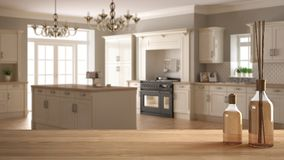Sobremesa o estante de madera con las botellas aromáticas de los palillos sobre cocina clásica borrosa con la isla, desig blanco  fotografía de archivo libre de regalías