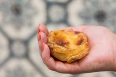 Sobremesa portuguesa Pasteis de nata na mão das mulheres imagem de stock