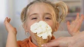 Sobremesa saboroso de espera da menina com os olhos fechados, lambendo o gelado com prazer vídeos de arquivo