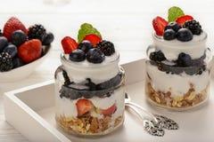 Sobremesa saudável do iogurte com muesli, morangos, amoras-pretas e mirtilos na tabela de madeira branca Imagem de Stock