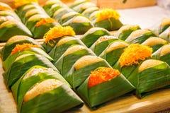 Sobremesa tailandesa: O arroz pegajoso doce com o creme cozinhado do ovo com variedades da cobertura envolvido com banana sae do  imagem de stock