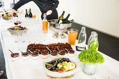 Sobremesas da restauração na tabela de bufete com vinho do serviço do homem no B fotos de stock royalty free