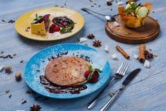 Sobremesas do restaurante Panquecas, gelado, bolo de queijo na madeira azul Imagem de Stock Royalty Free