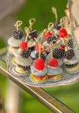 Sobremesas francesas do bolinho de amêndoa com as bagas e os frutos enchidos com o creme para o aniversário e o casamento fotos de stock royalty free