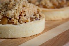 Sobremesas pequenas do tarte de maçã na placa de corte de madeira Imagem de Stock Royalty Free