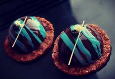 Sobremesas pretas e azuis na base da cookie imagens de stock