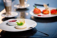 Sobremesas saborosos com os copos de café na tabela no restaurante Foto de Stock Royalty Free