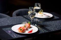 Sobremesas saborosos e vidros da água na tabela no restaurante Fotografia de Stock Royalty Free