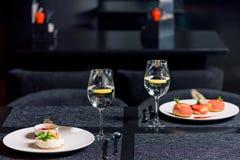 Sobremesas saborosos e vidros da água na tabela no restaurante Fotografia de Stock