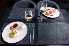 Sobremesas saborosos e vidros da água na tabela no restaurante Imagem de Stock Royalty Free