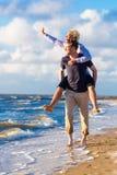 Sobreposto carreg da mulher do homem na praia Imagens de Stock Royalty Free