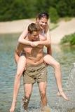 Sobreposto - os pares felizes apreciam o sol no lago Imagem de Stock Royalty Free