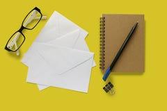 Sobres de la letra, vidrios del ojo, cuaderno, pluma y un clip de la carpeta fotos de archivo