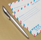 Sobres internacionales del correo aéreo y una pluma Fotografía de archivo