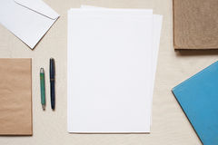 Sobres y hojas de papel vacíos en la tabla Foto de archivo