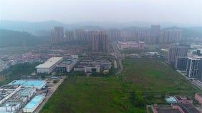 Sobrevuelo de pequeñas fábricas chinas, de montañas y del área residencial en el fondo metrajes