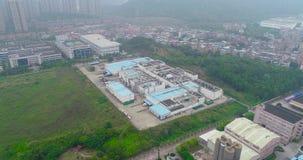 Sobrevuelo de pequeñas fábricas chinas, de montañas y del área residencial en el fondo almacen de video