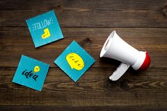 Socail media announcements concept. Megaphone near social media icons on dark wooden background top view.  stock photos