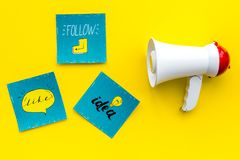 Socail media announcements concept. Megaphone near social media icons on yellow background top view royalty free stock photos