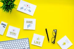 Socail media icons on work desk of marketing expert. Digital promotion of goods and services. Yellow background top view.  stock image