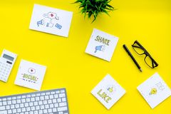 Socail media icons on work desk of marketing expert. Digital promotion of goods and services. Yellow background top view stock image