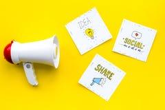 Socail zawiadomień medialny pojęcie Megafon blisko ogólnospołecznych medialnych ikon na żółtego tła odgórnym widoku Obraz Stock