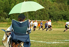 Soccar Mom. A mom sits and watches the kids play soccer in the field Stock Photos