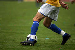 Soccer. A soccer player playing the ball on the grass royalty free stock photos
