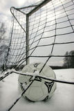 Soccer. A soccer ball in a goal. Soccer game in winter Stock Images