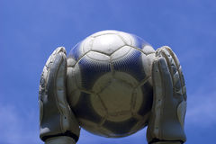 Soccer. Ball being held by the keeper against a sky background royalty free stock photography