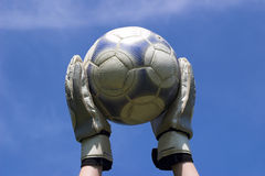 Soccer. Ball being held by the keeper against a sky background stock photography