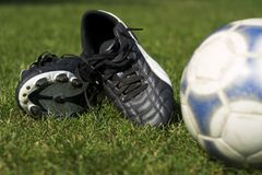 Soccer. Boots and ball laid on grass royalty free stock photography