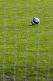Soccer. Ball staying in the grass. Blurred net visible in the foreground Stock Image