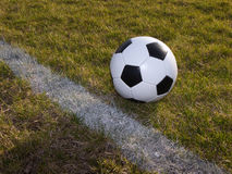 Soccer. Photo of a soccer ball near a white line on the grass Royalty Free Stock Photo