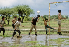 Soccer. A group of adolescents and children playing soccer in a waterlogged field Stock Photos