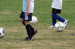 Soccer. Legs and balls of kids playing soccer Royalty Free Stock Image