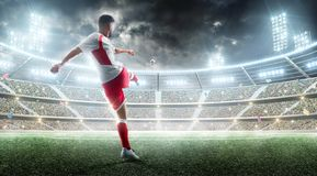Soccer action. Professional soccer player kicks a ball on the night soccer stadium with fans and flags. 3d football stock photography