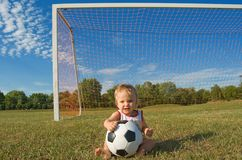 Soccer baby. Year old baby holding a soccer ball in front of the goal Stock Images