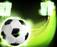 Soccer background. Ball illuminated by spotlights on a green background. Abstract sports background Stock Photo