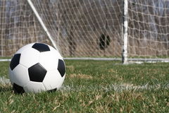 Soccer ball. Checkered soccer ball with a goal in the background Royalty Free Stock Photos