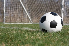 Soccer ball. On the field with a faded goal in the background Stock Image