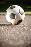 Soccer ball on asphalt Stock Photos
